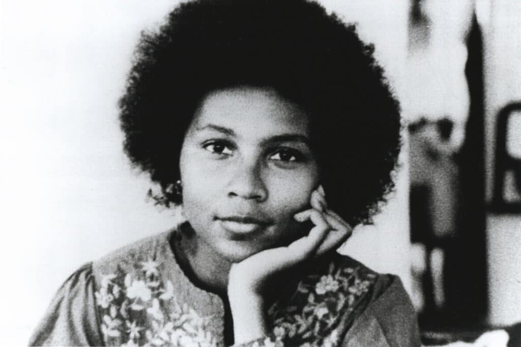 Black and white portrait of bell hooks who looks pensively at the camera while resting her chin on her palm.