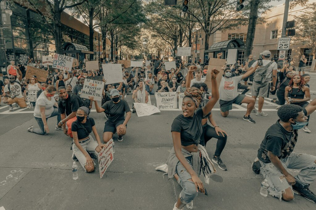Black Lives Matter protestors kneel in the middle of a road for social justice, holding up a fist.