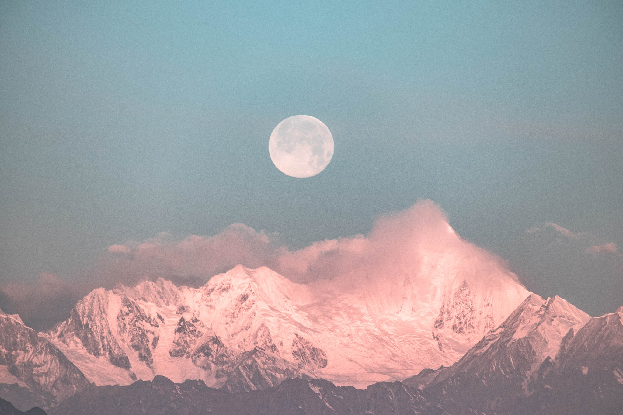 Pale full moon rising over snow-capped mountains