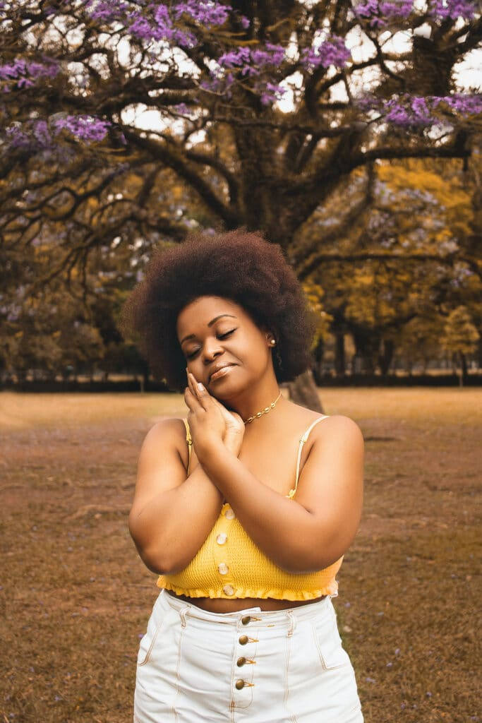 Black woman with a yellow top and white jeans loves herself, improving her health and wellbeing because she listens to intersectional feminist podcasts on self-care.