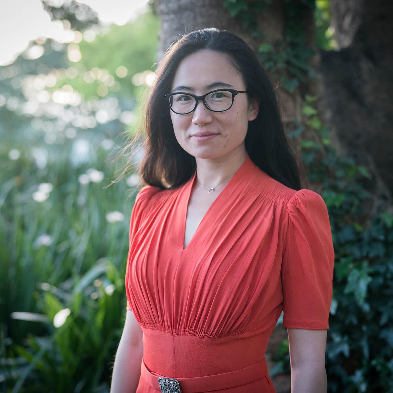 Helena Liu, the creator of this blog, stands in a forest in a coral dress ready to fight for social justice