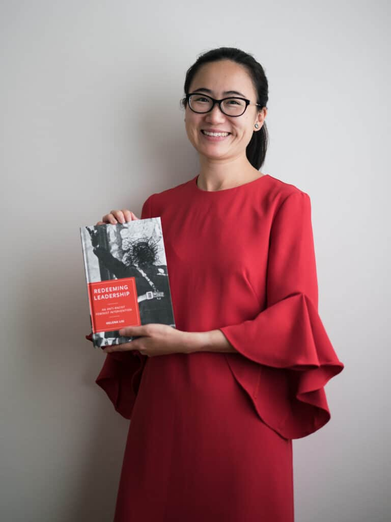 Helena Liu holds up a copy of her book, Redeeming Leadership, for intersectional feminist leadership practices towards social justice