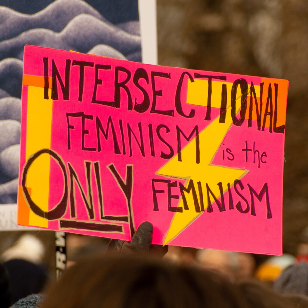 "A sign at a protest saying ""intersectional feminism is the only feminism"", highlighting the importance of reading more intersectional feminist books"