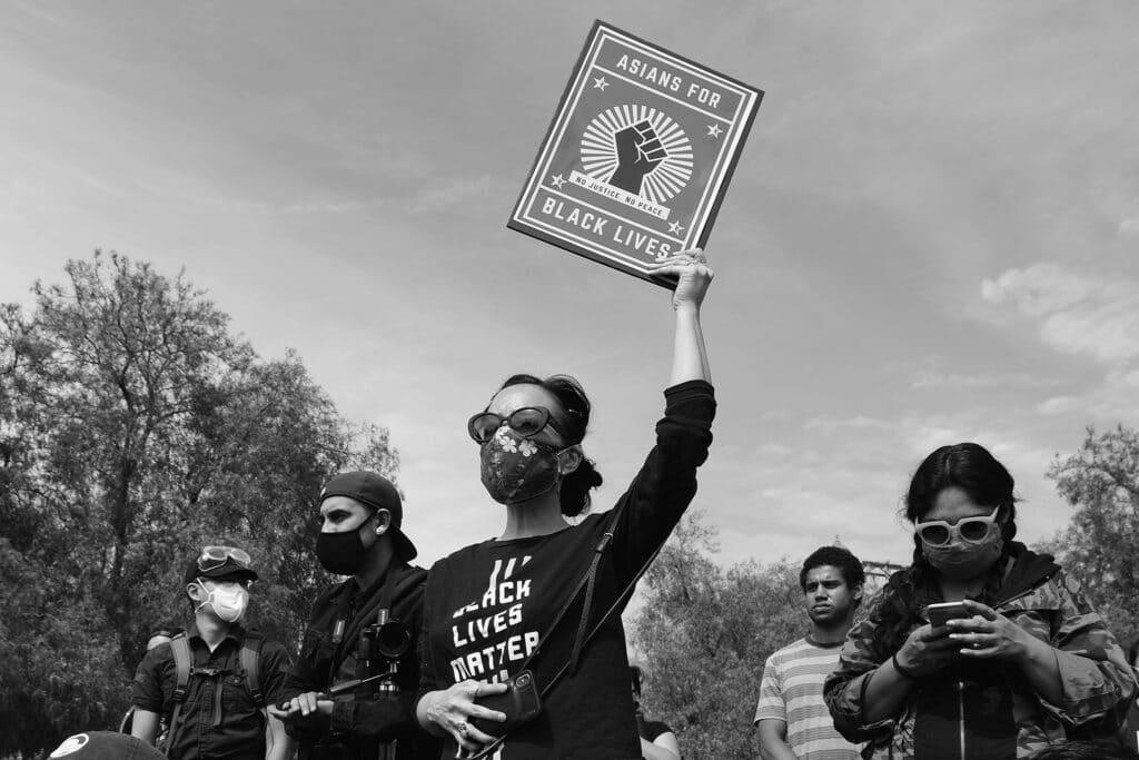 "Intersectional Black Lives Matter protestor holding up sign that says ""Asians for Black Lives"""