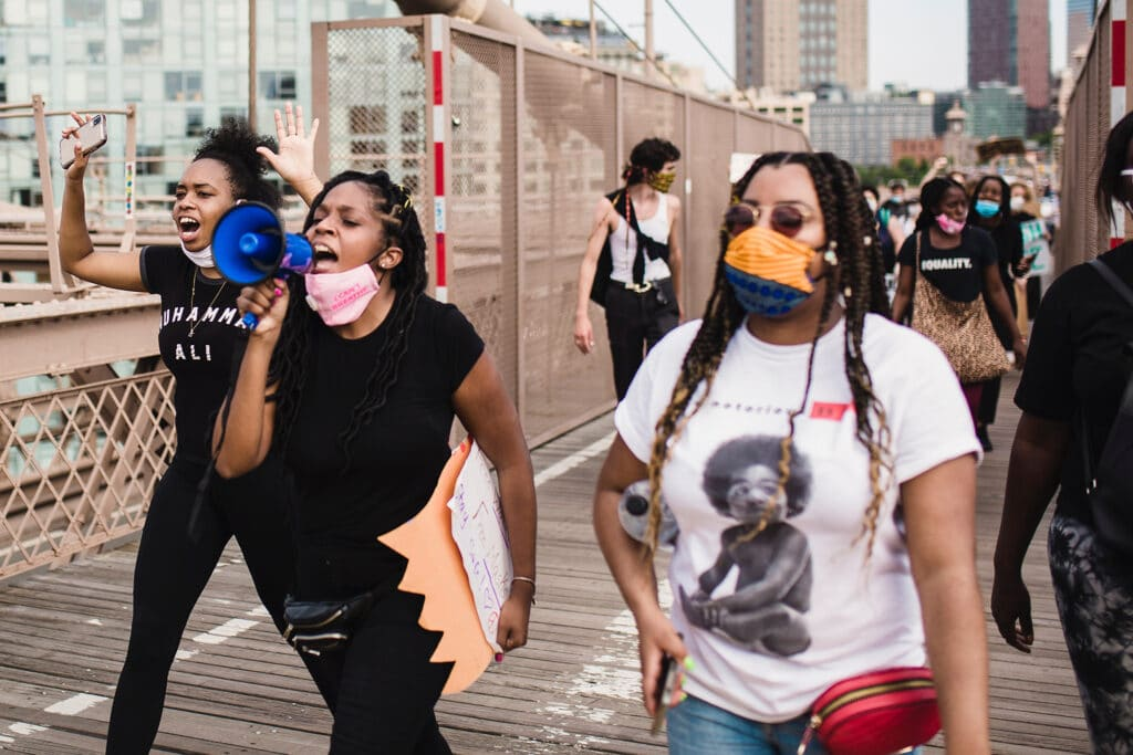Black women activists marching in a Black Lives Matter protest, symbolizing the intersectional feminist podcasts created by activists.