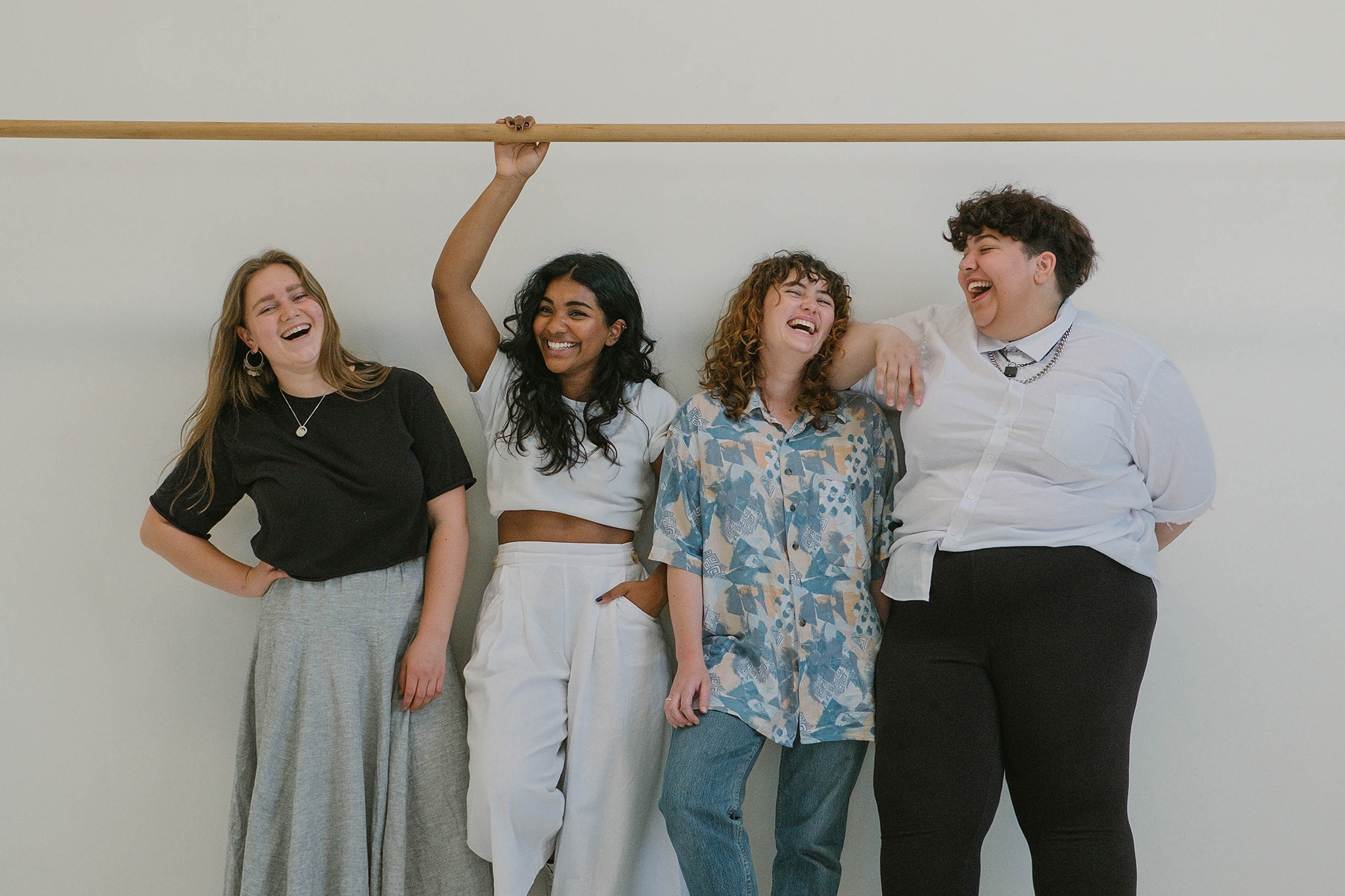 Four women laughing together in a diverse and inclusive workplace