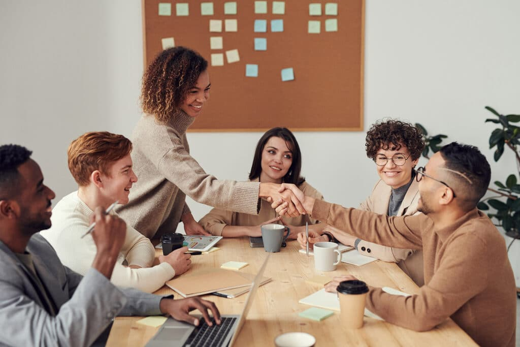 Intersectionality in the workplace with six smiling staff members sat around a table as two of them reach across the table to shake hands.