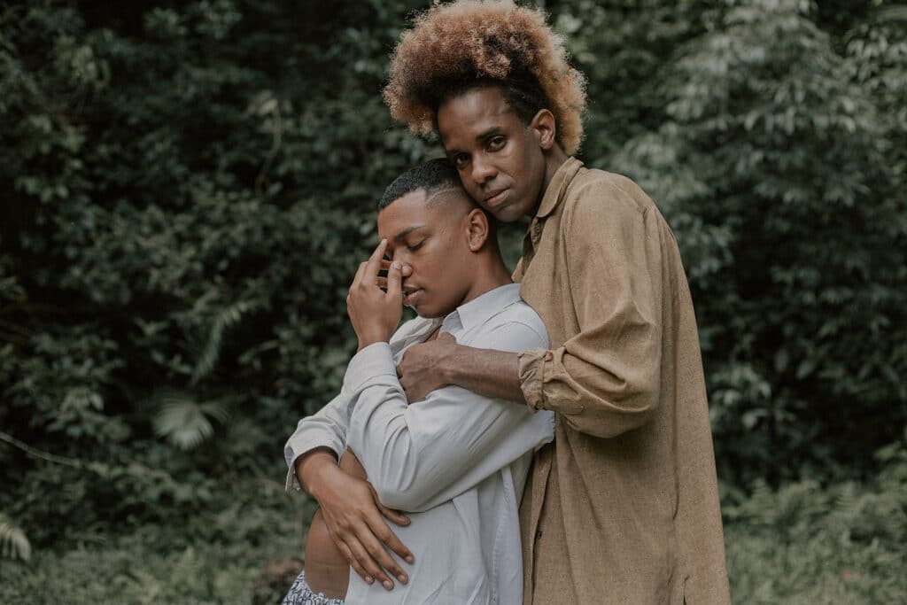 Two Black men holding each other in a gentle embrace in the forest, representing the importance of LGBTQIA+ justice within intersectionality.