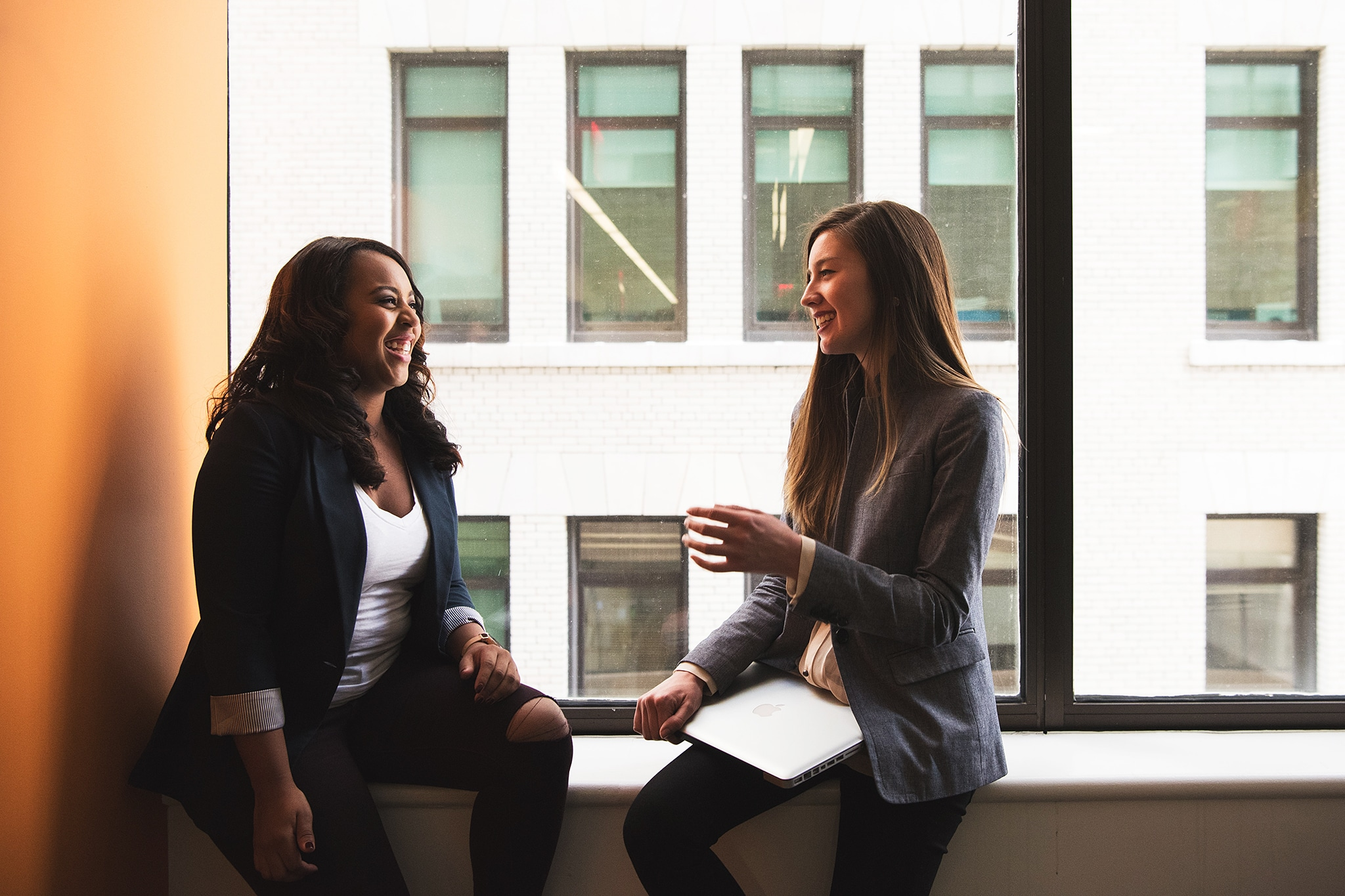 Two joyous women of color discussing intersectionality in the classroom
