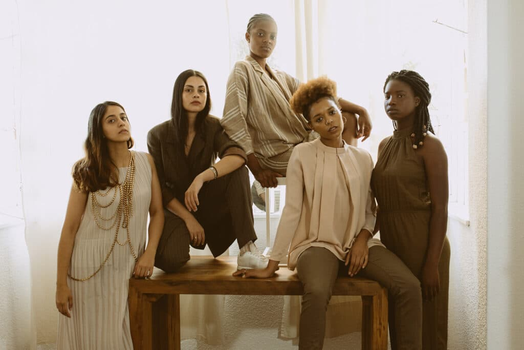 Five strong, beautiful Black and Brown women standing and sitting around a table, looking intensely at the camera.