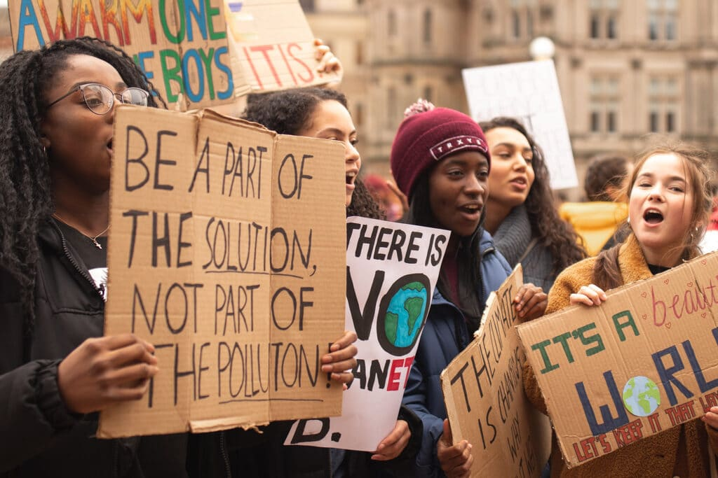 Young women demonstrating social justice activism for the environment, showing awareness for feminist standpoint and intersectionality