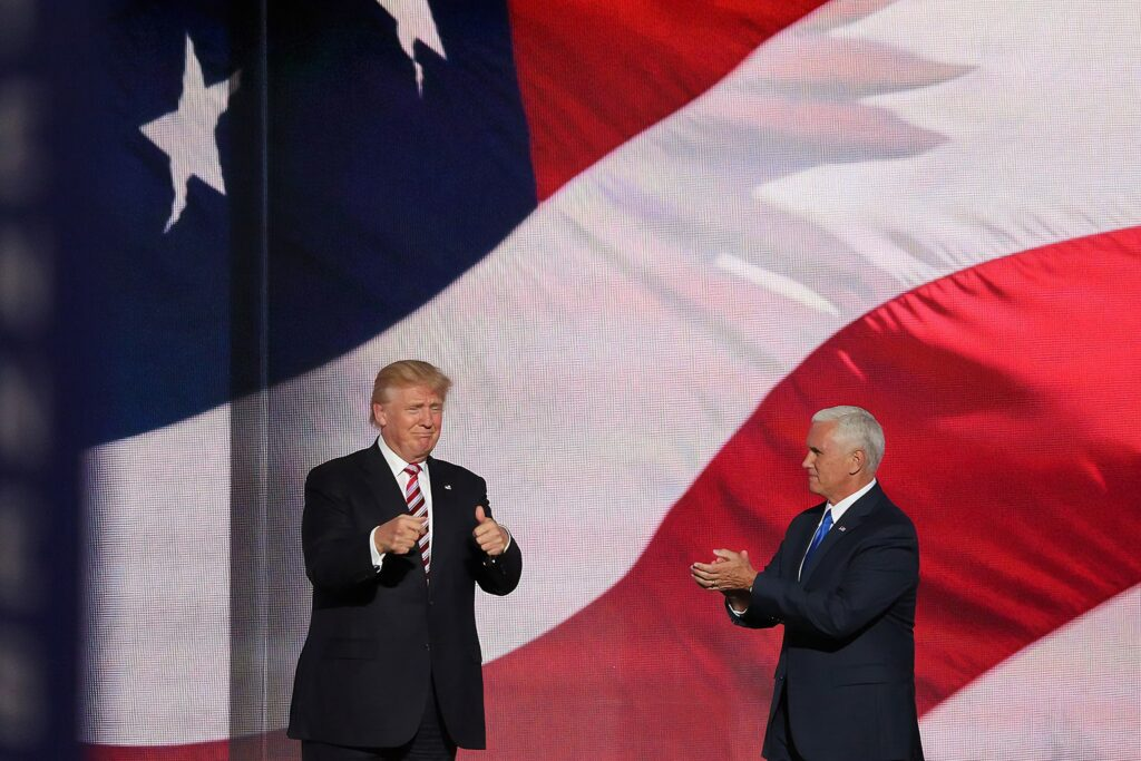 Donald Trump giving the thumbs up while Mike Pence applauds him in front of a large screen of the American flag highlights the urgent need for intersectional feminist leadership.