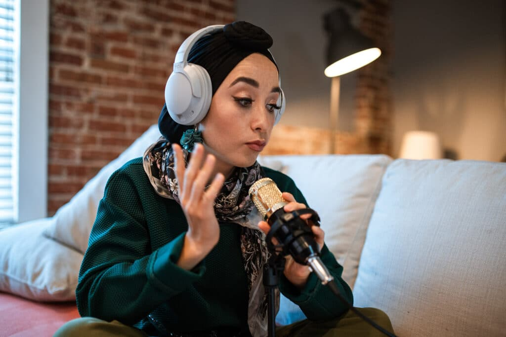 A Muslim woman sits on a couch with silver headphones holding a microphone in front of her, about to record her intersectional feminist podcasts.