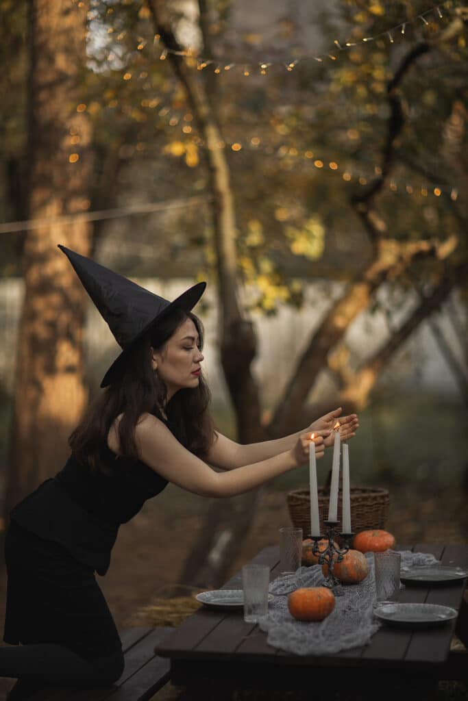 Witch in a black dress lights white taper candles on a candelabra, setting up for a dinner party in the woods to celebrate with a full moon ritual