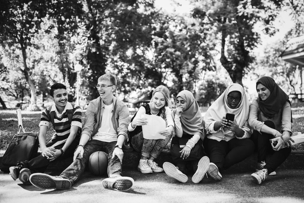 Group of six diverse students sitting on the edge of the pavement chatting and laughing with each other, showing the value of teaching social justice