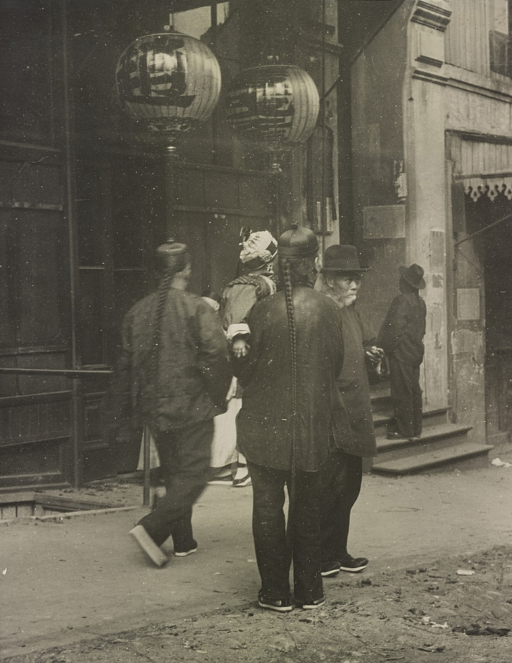 An old sepia photograph showing Chinese migrants walking down the street underneath lanterns, highlighting the rich history of Chinese migration to Western countries