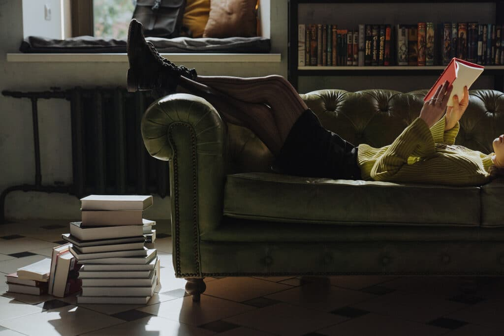 A woman lays on her back on an olive sofa reading with a pile of books by her feet, joining in Disorient's intersectional feminist reading challenge