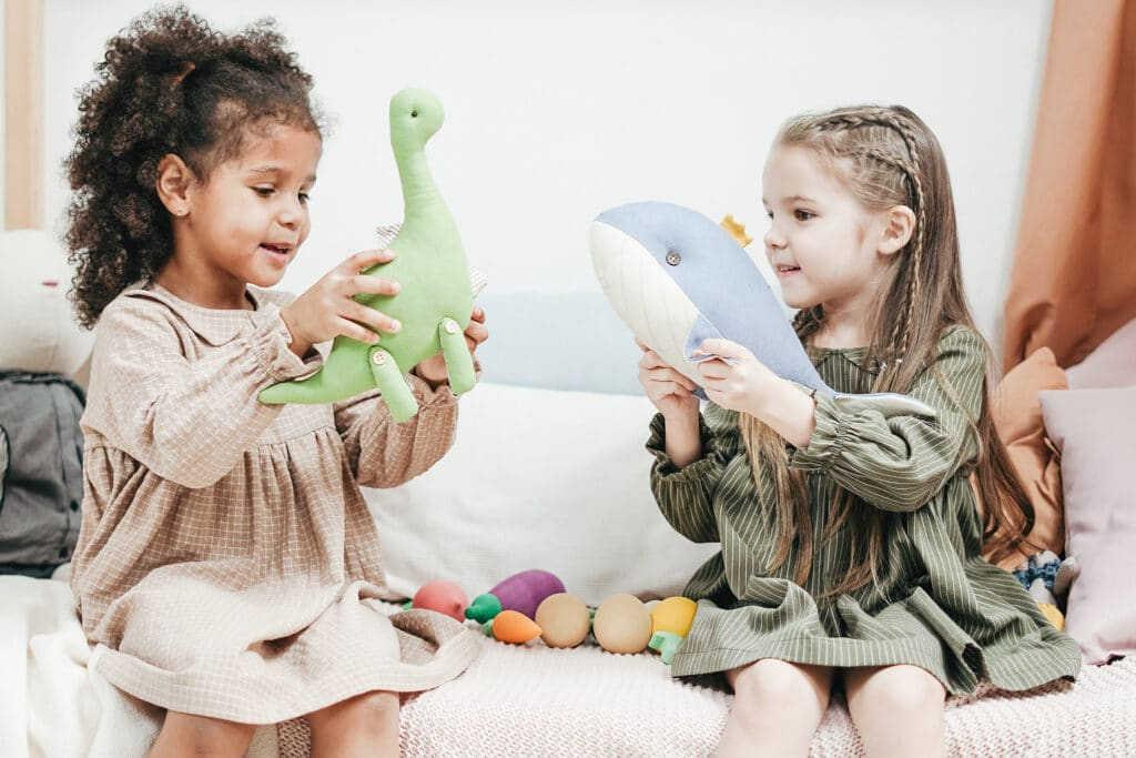 A Black girl plays with a green dinosaur toy and a white girl who holds up a blue whale toy. Their friendship represents how racism is learned.