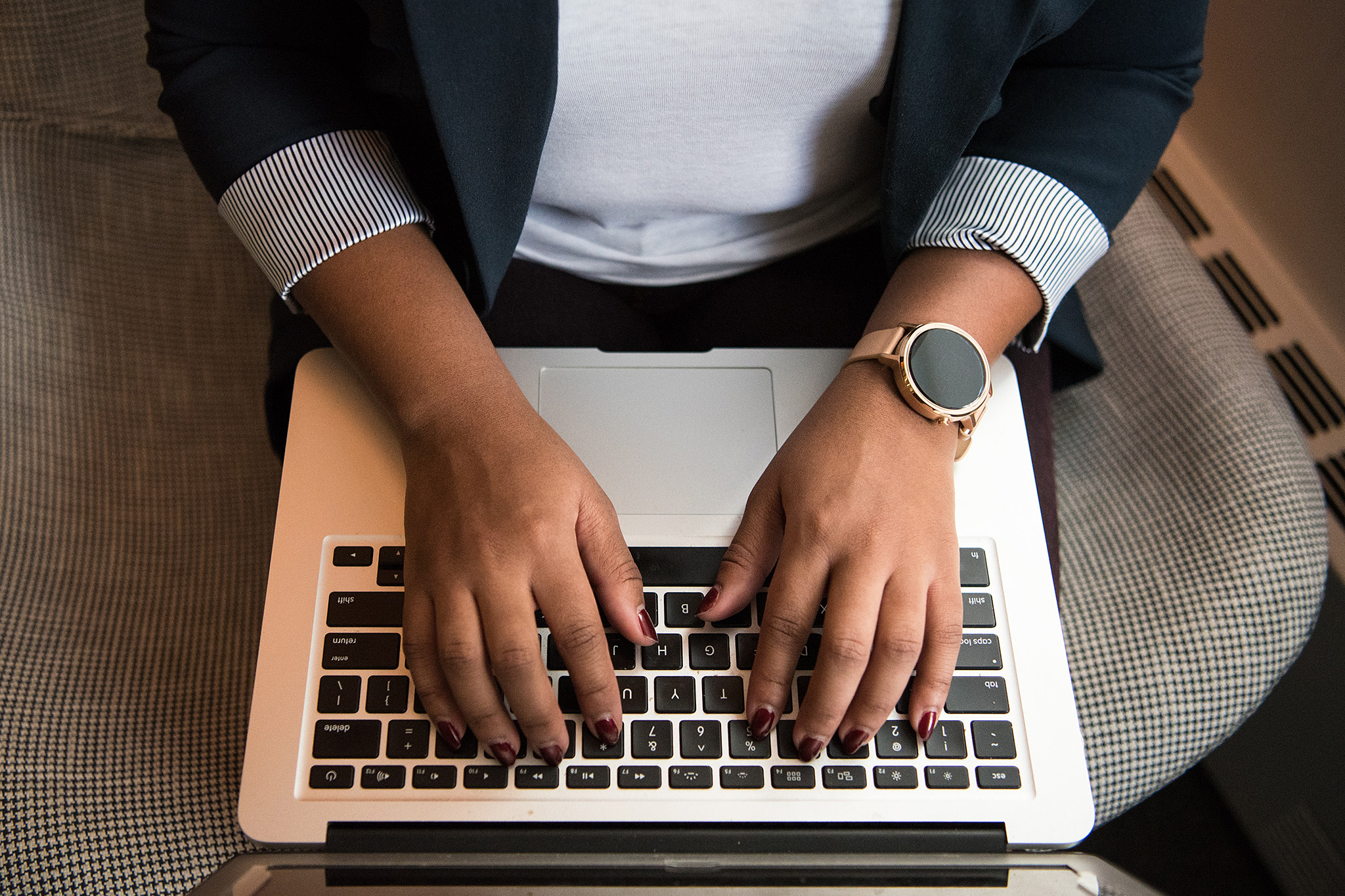 Closeup of woman's hands typing on a laptop keyboard, representing an activist blogging about social justice politics