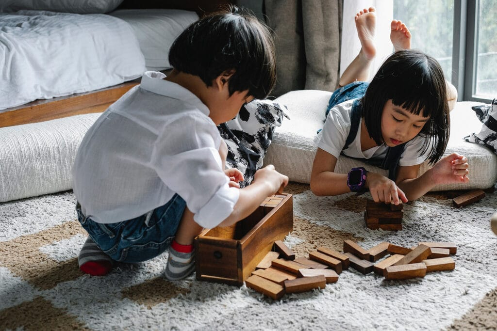 Two children playing with wooden blocks on a rug in a bedroom, highlighting the ways we begin the social construction of identity from childhood