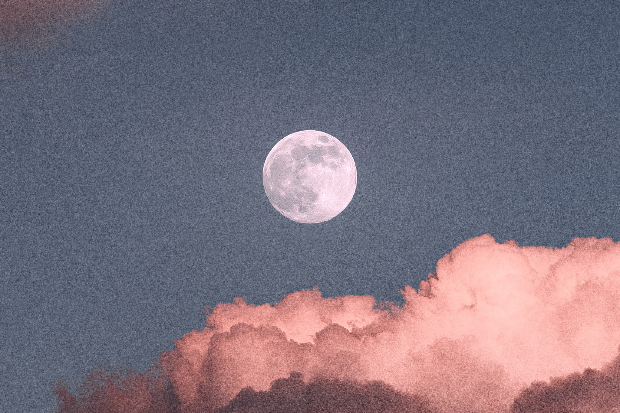 Full moon in the gray sky among pink clouds, time to perform a full moon ritual to raise power