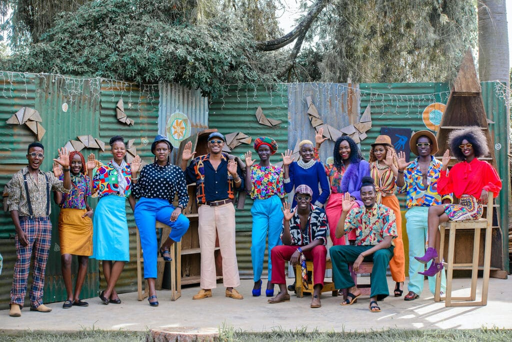 Thirteen people are dressed in beautiful colorful clothes and holding up a hand to the audience, representing the idea that joy as resistance should be shared within a community