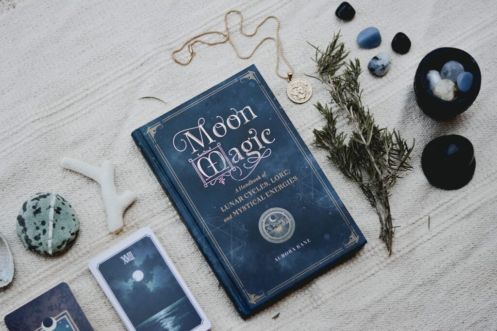 Book called Moon Magic on a tablecloth with plants, stones, crystals, and tarot cards, representing the value of a spiritual activist practice which can be supported by an altar