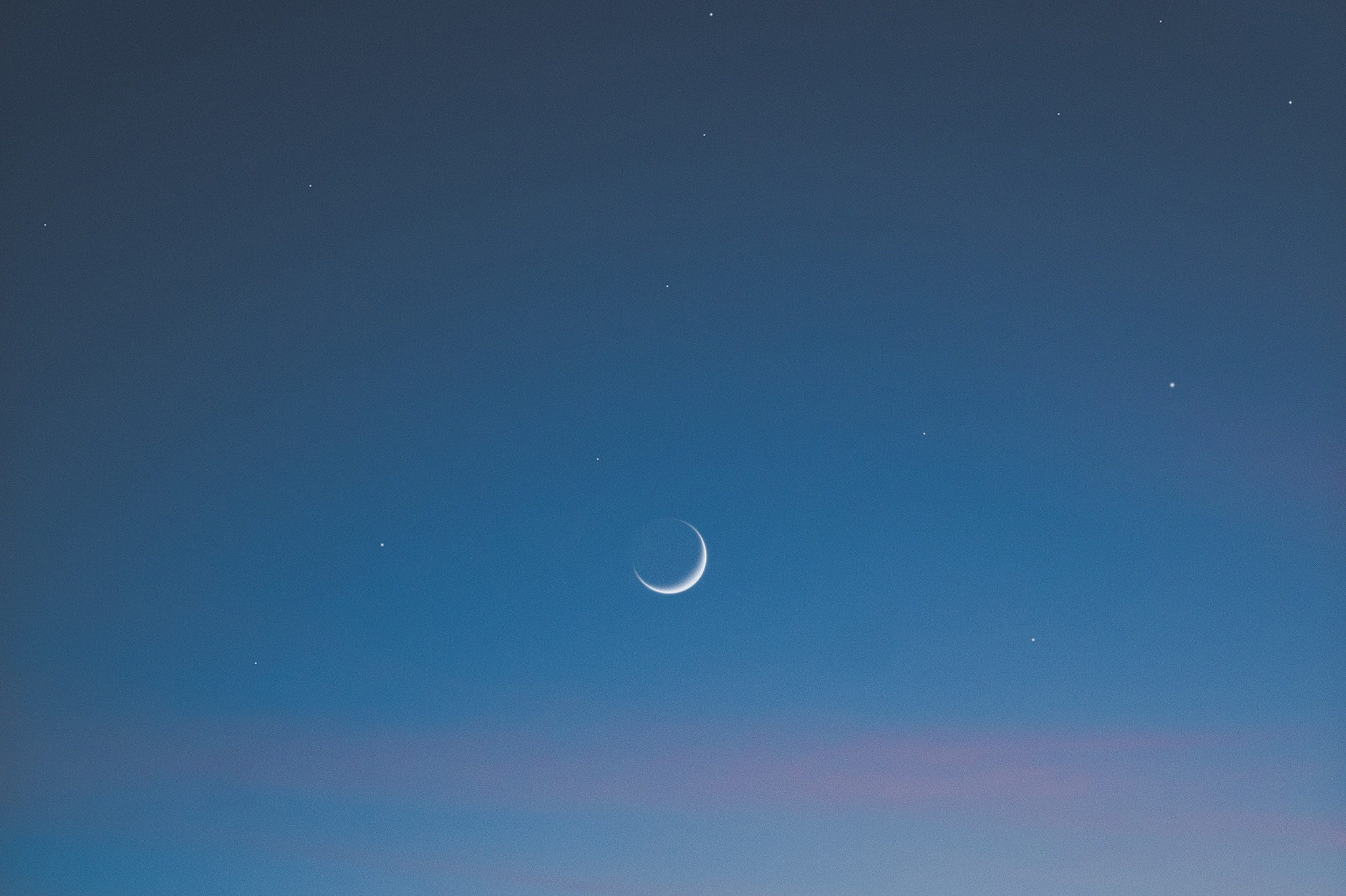 New moon hanging in a blue and pink sky, representing the time to perform a new moon ritual and set intentions for the next lunar cycle.