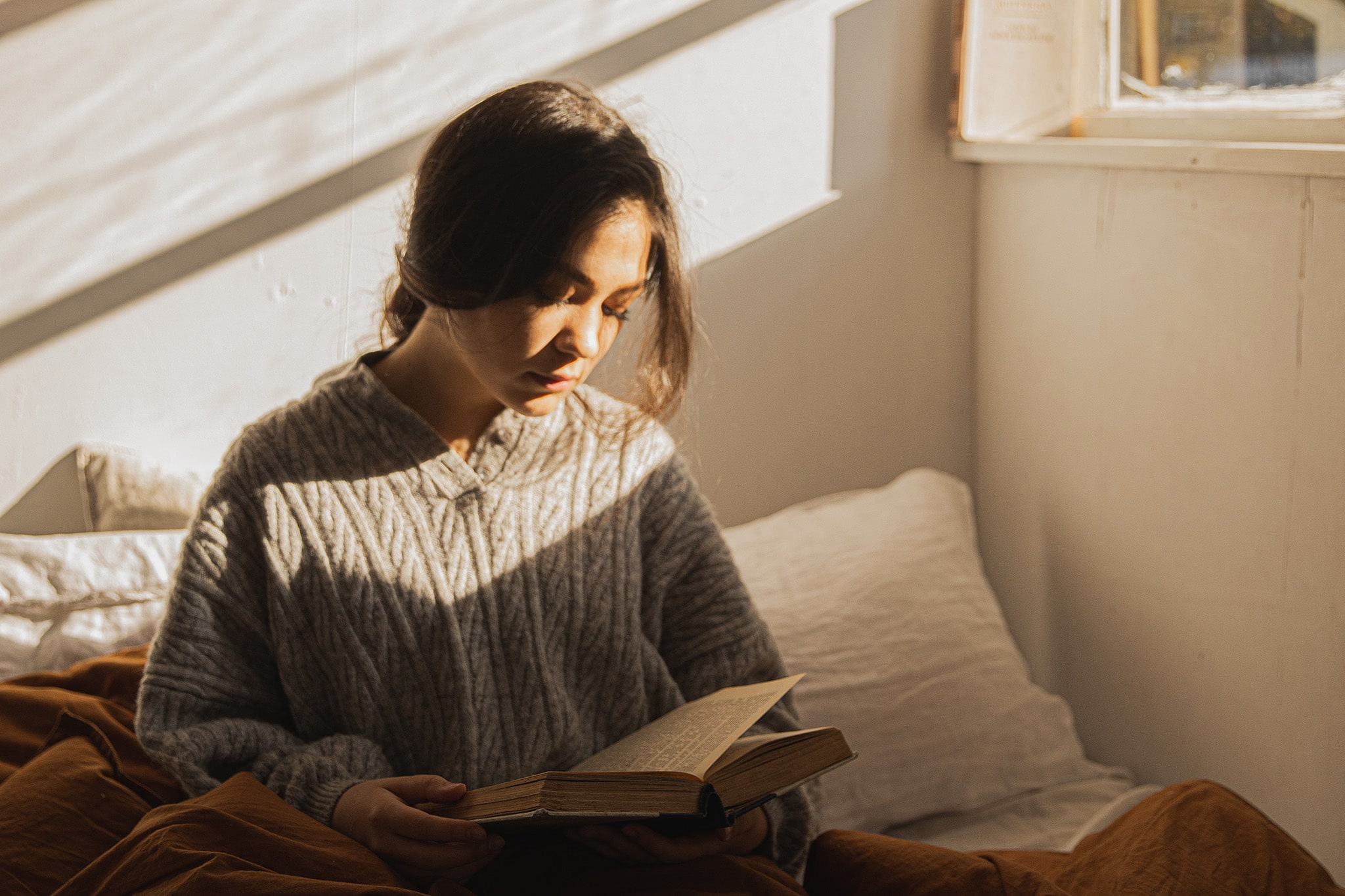 Woman reads a book in bed about feminist standpoint theory and intersectionality underneath the afternoon sunlight.