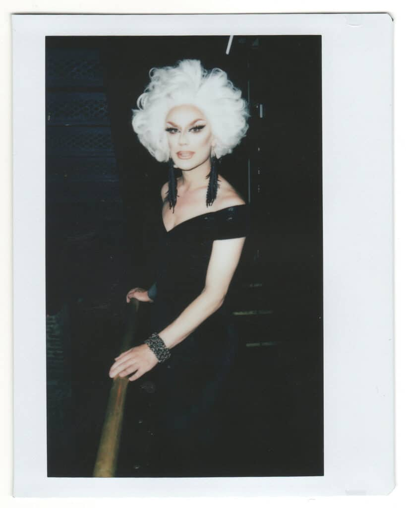 Polaroid of a glamorous drag queen with platinum blonde hair, a long, elegant black gown, and long black beaded earrings, representing the social construction of identity