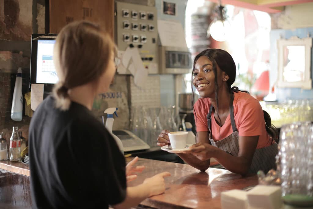 A Black woman barista wearing a pink t-shirt and grey apron is smiling and handing a cup of coffee over to a customer in a café, representing the multiple jeopardies of gender, race, and class faced by Black women and the importance of intersectional feminism and capitalism