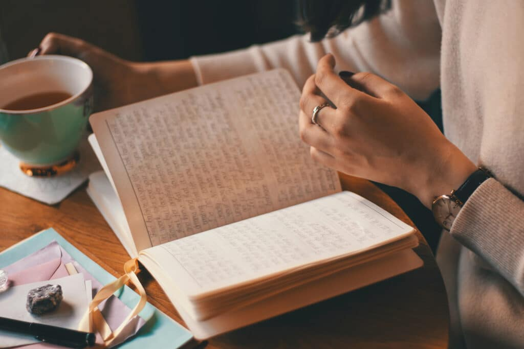 Closeup of a woman's hands over a beautiful handwritten journal while she grasps a teacup with her right hand, symbolizing the value of journaling as self-care through anti-racist feminist and queer writing prompts