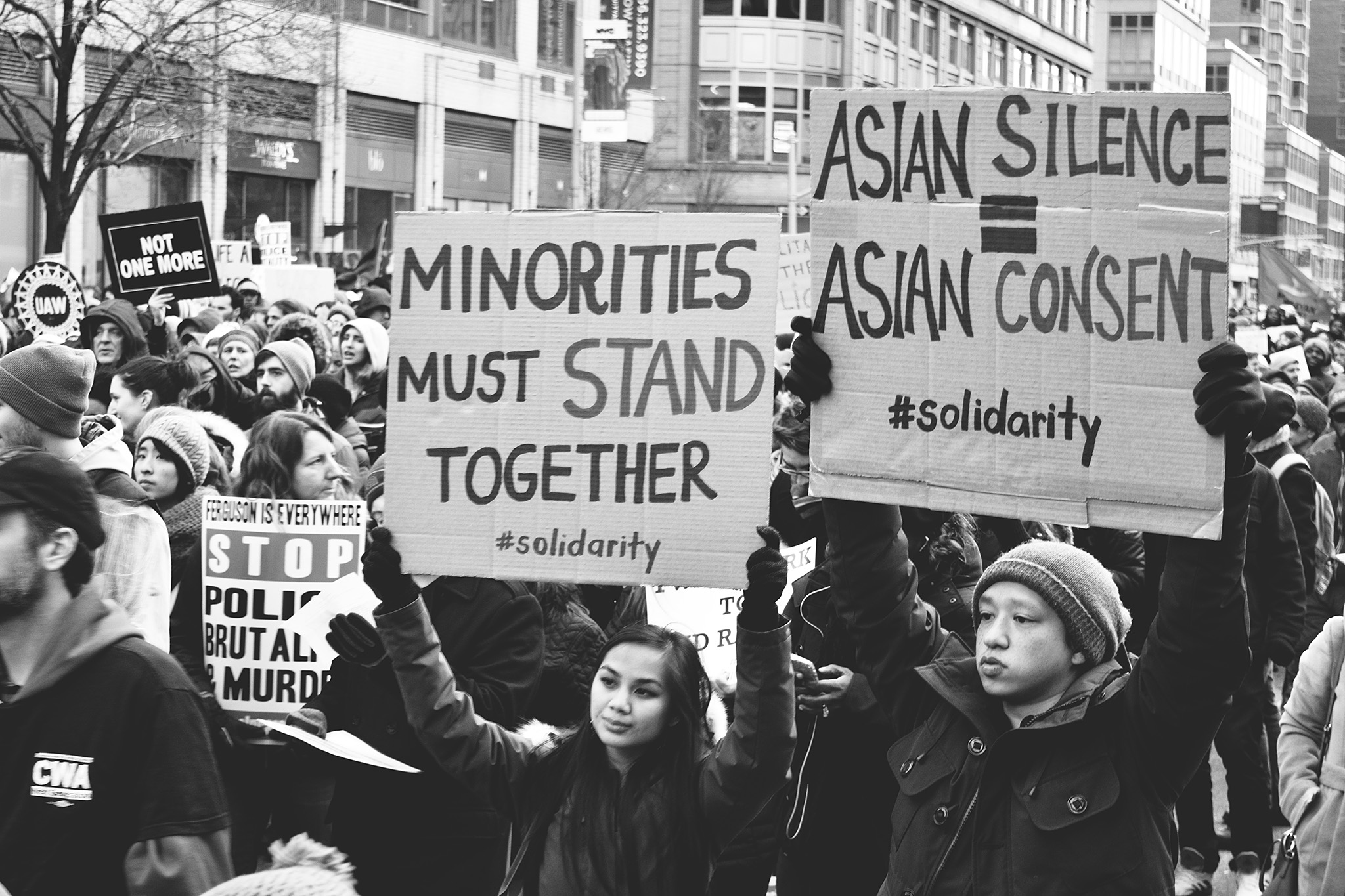 """Asian American racial justice protestors in New York City in 2014, focussing on two people in the foreground holding up cardboard signs that read """"minorities must stand together #solidarity"""" and """"Asian silence = Asian consent #solidarity"""", challenging the model minority myth"""