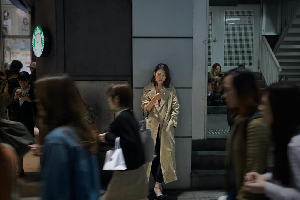 A busy street with multiple people walking across the foreground, focused on an Asian woman in a beige trenchcoat leaning against the wall checking her phone, representing the pervasive construction of Asians within the model minority myth