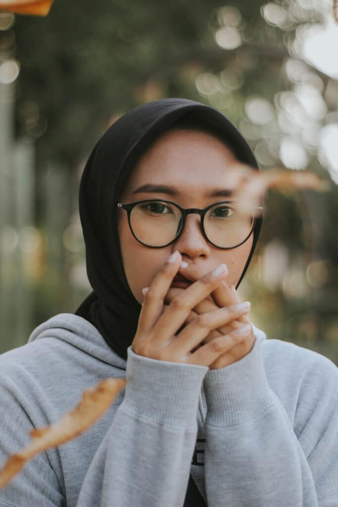An Asian woman in a hijab and glasses holds her hands over her mouth, suggesting the fear and anxiety that can be experienced by people who face workplace harassment and bullying