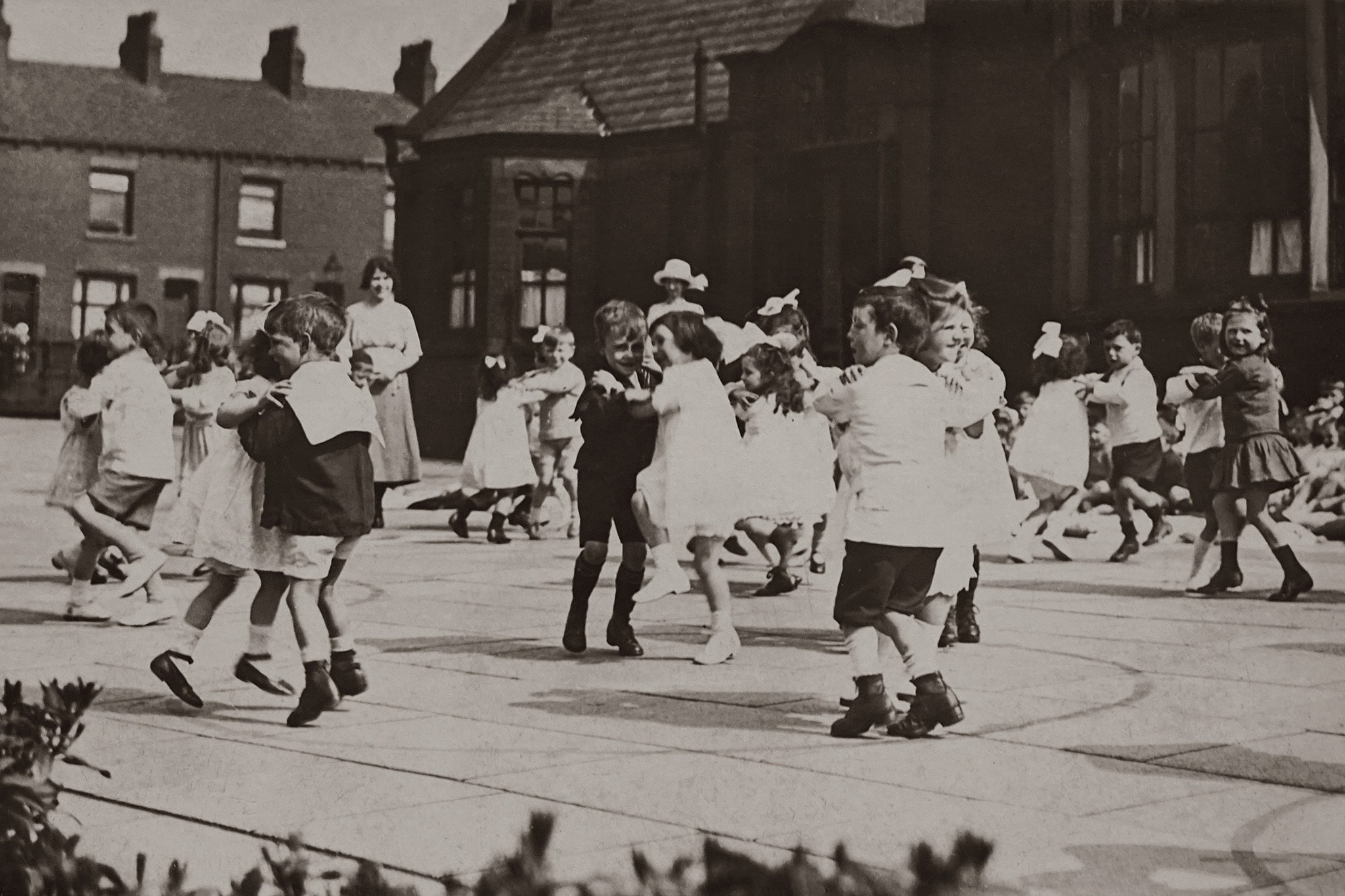 Children learn how to perform gender identities in an old sepia photograph where boys and girls and paired off with each other on the playground