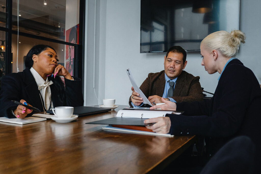 Three employees sit around a table discussing documents, representing corporate diversity and inclusion reflected in often superficial displays of visible gender and racial difference