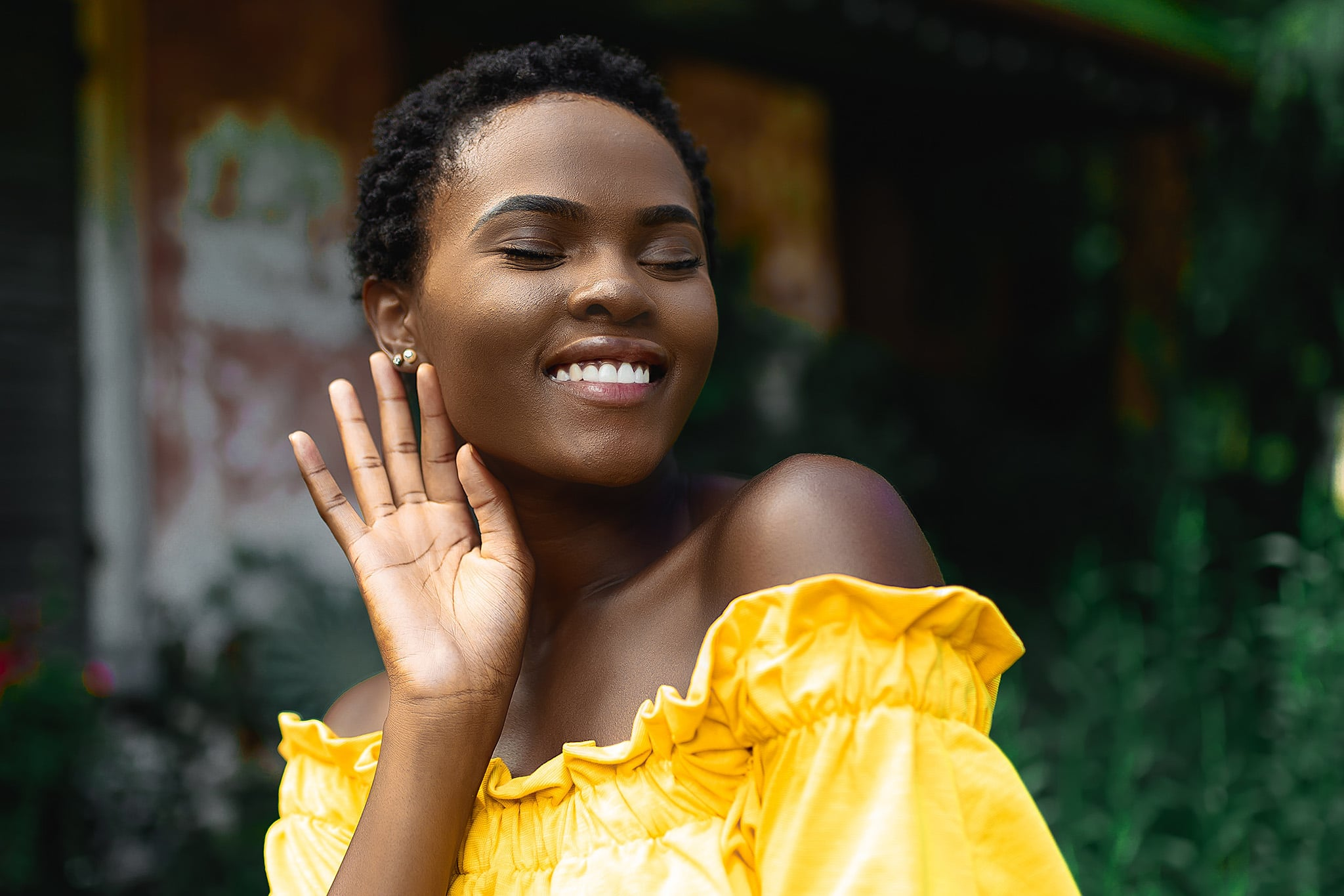 A Black woman is smiling with pure joy in an off-the-shoulder yellow dress symbolizing joy as resistance in intersectional feminism