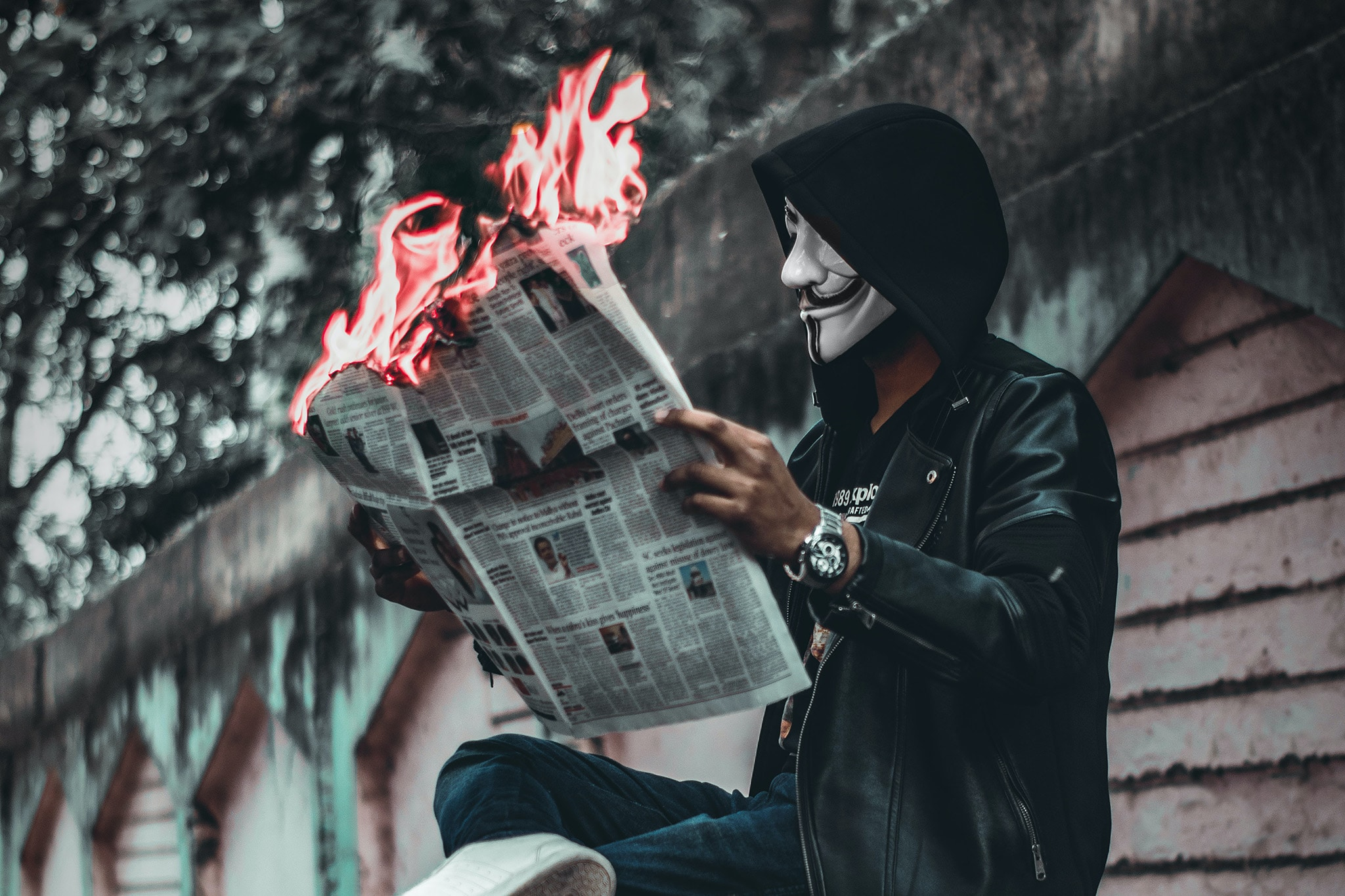 A Black man in a hoodie and Guy Fawkes mask is reading a newspaper that is on fire, symbolizing Marxist critiques and resistance under capitalism