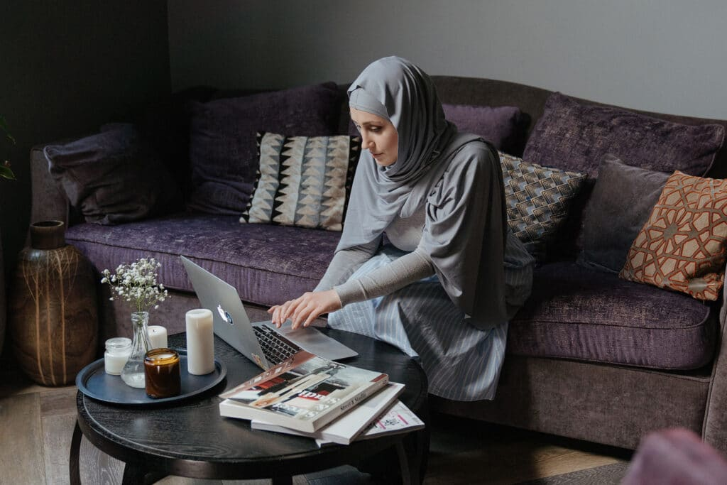 A Muslim woman sitting in her living room on a large couch is using her laptop on her coffee table, suggesting the online hatred that is often targeted to people with multiple intersecting marginalities