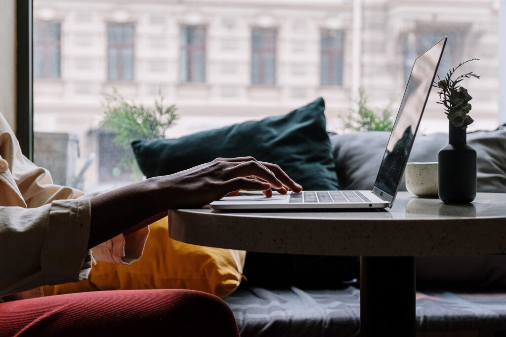 Silhouetted hands of someone using a laptop in their living room in front of a large window showing the city outside
