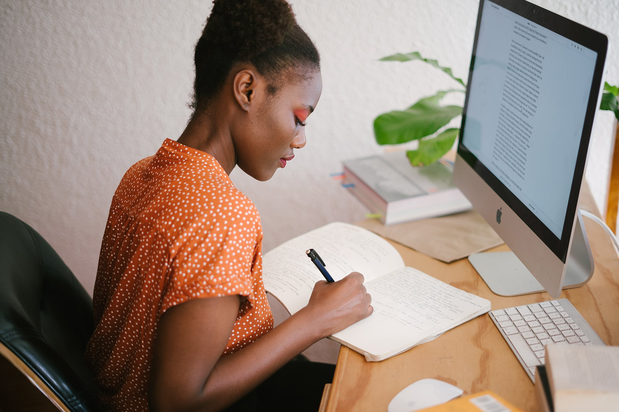 Black woman scholar-activist is working at a desk in front of her computer while writing in a notebook, representing the intellectual work of scholar-activism