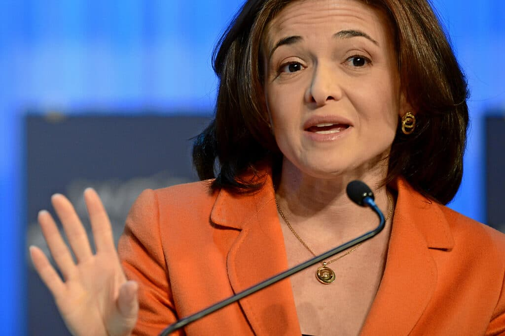 Sheryl Sandberg, author of Lean In, giving a speech in an orange suit jacket