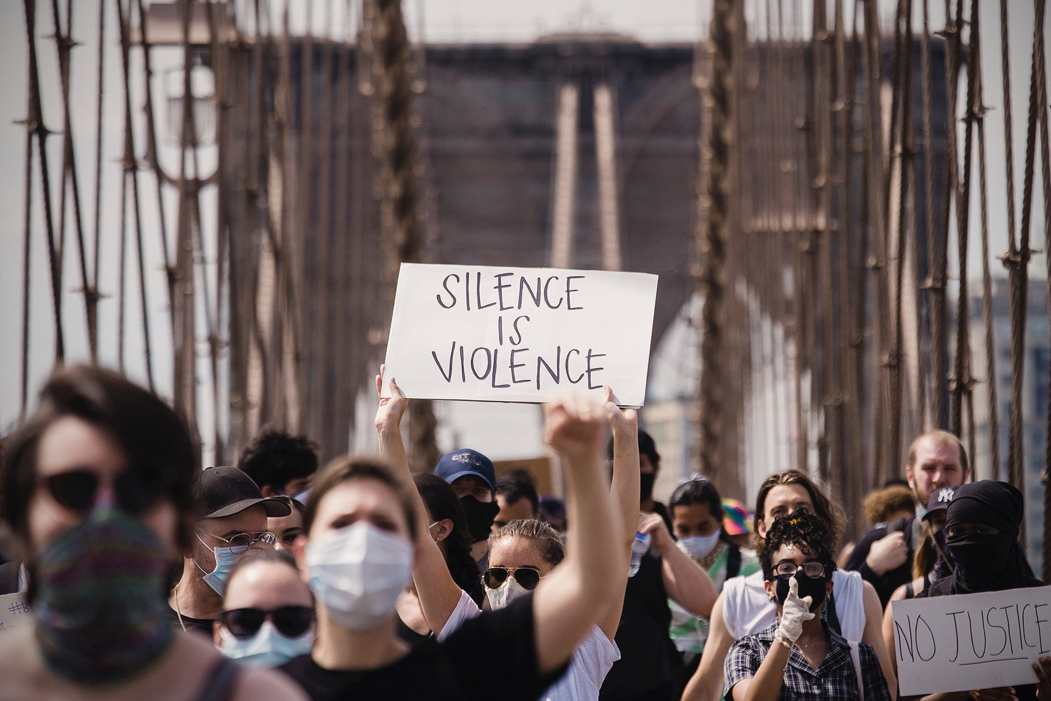 "Protestors on bridge with one holding up a cardboard sign reading ""silence is violence"", highlighting the ways we can support BLM without money"