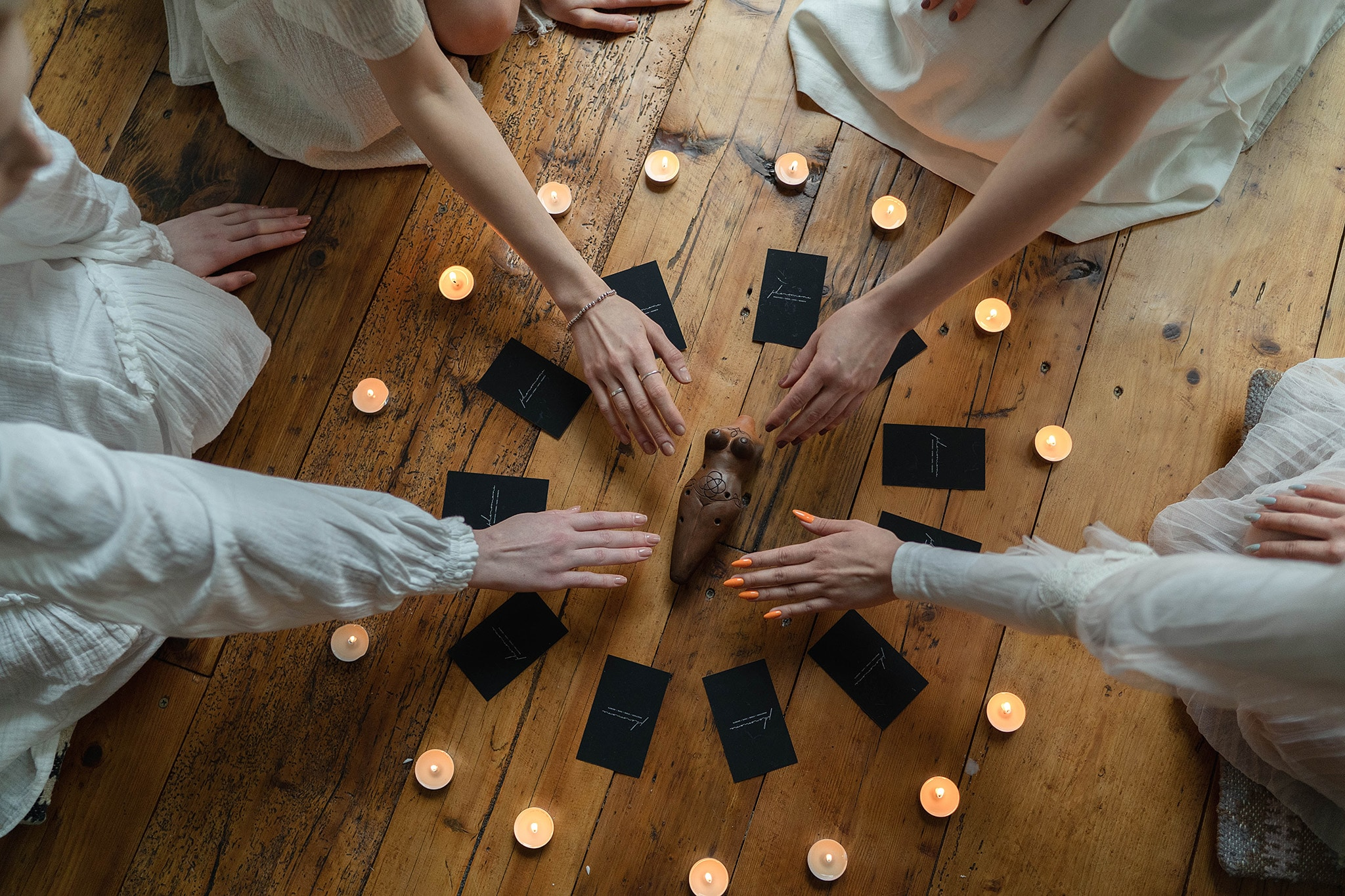 An aerial view of four arms reaching into the center of the image where tarot cards are laid out in a circle among tealight candles, symbolizing the activist witches who use tarot for social justice