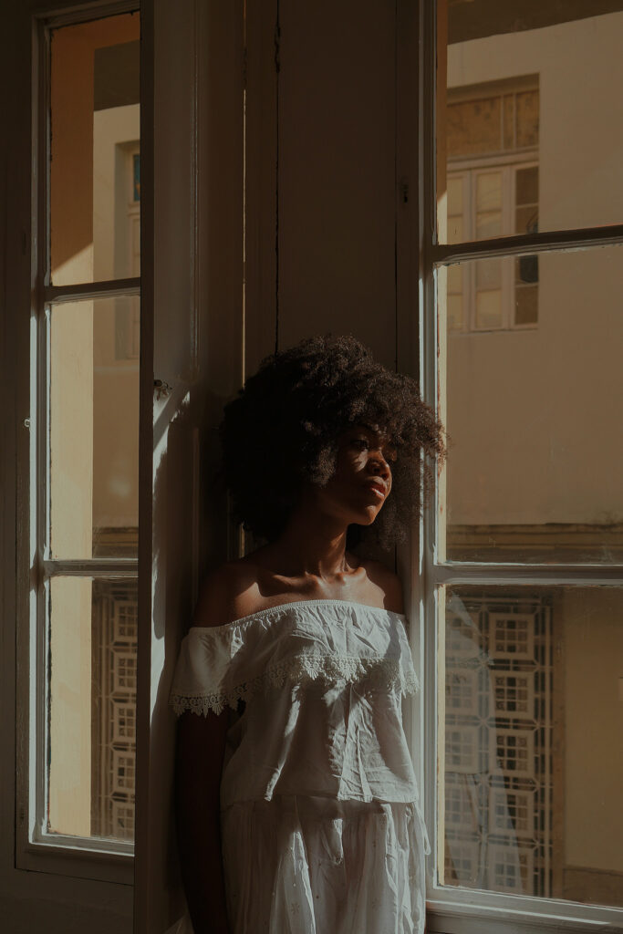 Black woman in a white dress leans against wall looking out a large window, looking sad, symbolizing the pain and suffering experienced with workplace bullying and harassment at work