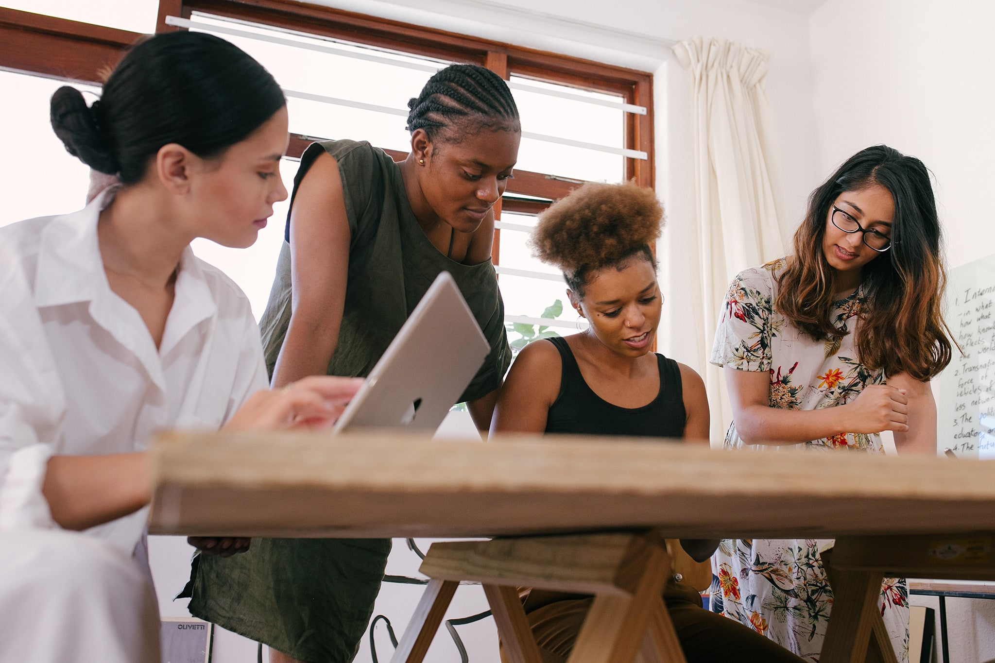 Four women are working over a desk deep in discussion, representing the diversity some corporations promote through policies and procedures at work