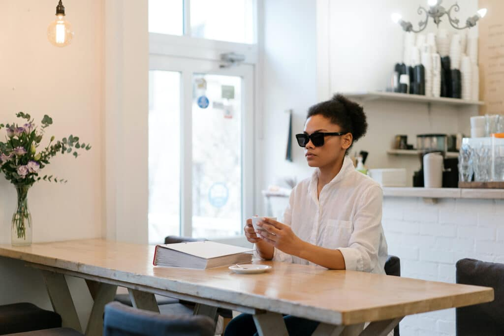 A blind Black woman is having coffee in a cosy café while a Braille book sits beside her. Coffee machine and coffee cups are neatly stacked in the background.