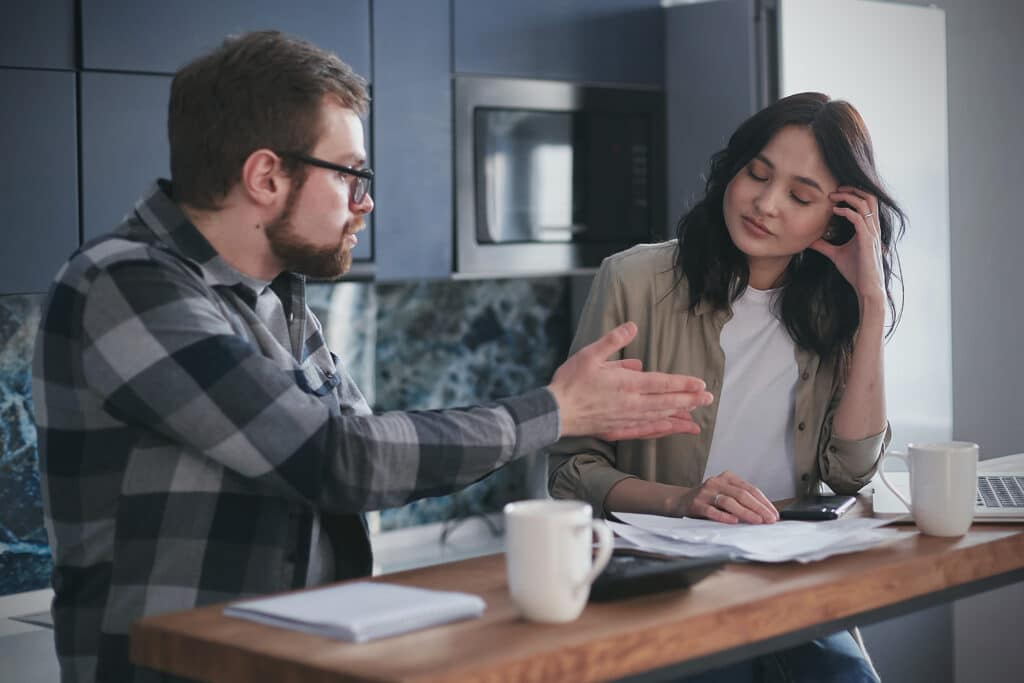 A white man is gaslighting a woman of color in an office kitchen who looks exhausted at his nonsense