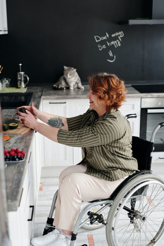A woman in a wheelchair wears an olive striped shirt and cream pants, chopping avocados in her kitchen while her tabby cat lays on the kitchen counter